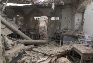 A woman visit her apartment damaged after shelling in Mariupol, Ukraine, Monday, Aug. 17, 2015. At least seven civilians and two Ukrainian troops were killed overnight today in eastern Ukraine as shelling from the warring sides intensified. The fighting between Russia-backed separatist rebels and Ukrainian government troops in the country's industrial heartland eased after a truce was signed in February. (AP Photo/Sergey Vaganov)